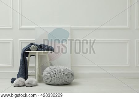 Knitted Pouf, Fuzzy Slippers And Decor Elements Near White Wall Indoors. Space For Text