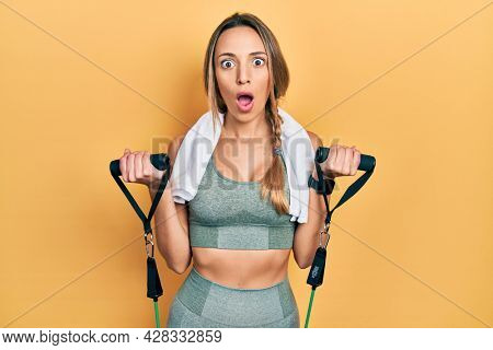 Beautiful hispanic woman training arm resistance with elastic arm bands afraid and shocked with surprise and amazed expression, fear and excited face.