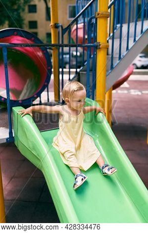 Little Girl In A Dress Slides Down A Slide On The Playground