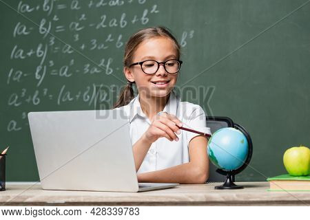 Smiling Schoolkid Pointing With Pencil At Globe Near Laptop And Blurred Chalkboard