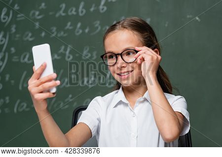 Smiling Schoolkid Touching Eyeglasses During Video Call Near Chalkboard
