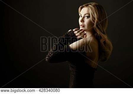 Portrait of a wealthy middle-aged woman with evening makeup and hairstyle posing in black dress on a black background. Luxury lifestyle. Cosmetology, plastic surgery, rejuvenation.