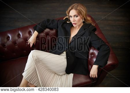 Portrait of a fashionable middle-aged woman with enlarged full lips sitting on a leather sofa. Fashion and Beauty. Cosmetology, plastic surgery, rejuvenation.
