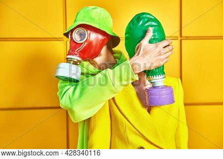 Love and the apocalypse. A man in a gas mask closes the eyes of a woman in a gas mask by a yellow industrial wall. Environmental disaster.