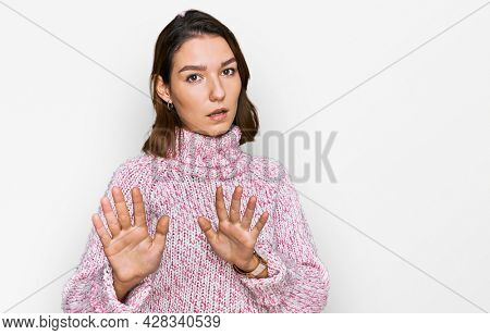 Young caucasian girl wearing wool winter sweater moving away hands palms showing refusal and denial with afraid and disgusting expression. stop and forbidden.