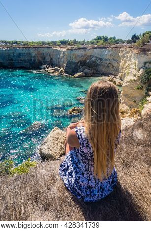 Torre Sant Andrea, Salento Sea Coast, Apulia, Italy. Young Woman In A Dress Sitting Overlooking The