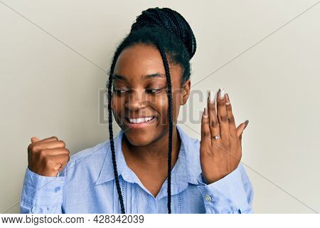 African american woman with braided hair wearing engagement ring pointing thumb up to the side smiling happy with open mouth
