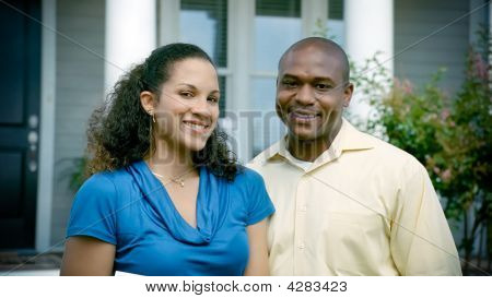 African American Couple Stands In Front Of House Smiling At Camera