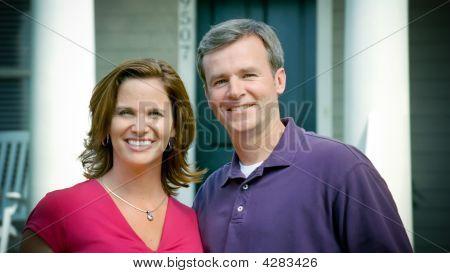 Caucasion Couple Stand In Front Of New Home