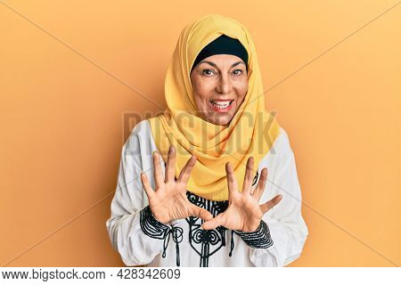 Middle age hispanic woman wearing traditional islamic hijab scarf disgusted expression, displeased and fearful doing disgust face because aversion reaction. with hands raised