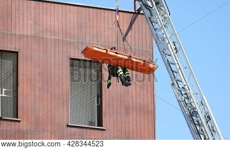 Brave Fire Brigade Recovers Wounded With A Stretcher Suspended In The Air With High Rescue Crane