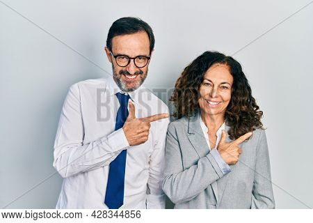 Middle age couple of hispanic woman and man wearing business office uniform cheerful with a smile of face pointing with hand and finger up to the side with happy and natural expression on face