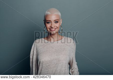 Millenial Young Woman With Short Blonde Hair Smiling Portrait On Blue Background
