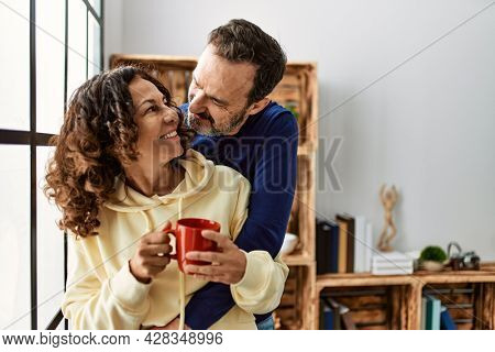 Middle age hispanic couple smiling happy and drinking coffee. Leaning on the window at home.