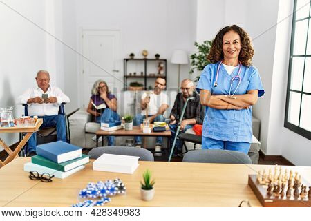 Middle age doctor woman smiling happy standing with arms crossed gesture at nursing home.