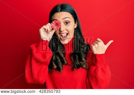 Young hispanic woman holding flower over eye pointing thumb up to the side smiling happy with open mouth