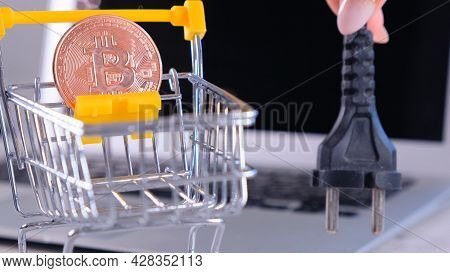 Cryptocurrency Bitcoin With Power Supply Socket. Hand Holding Plug Have Computer Monitor In The Back