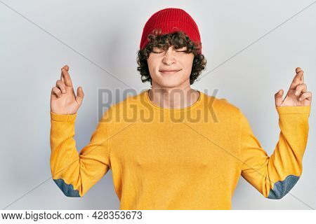 Handsome young man wearing wool hat gesturing finger crossed smiling with hope and eyes closed. luck and superstitious concept.