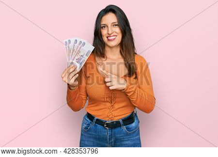 Beautiful hispanic woman holding russian 500 ruble banknotes smiling happy pointing with hand and finger