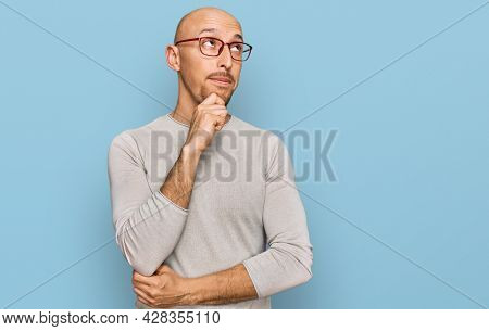 Bald man with beard wearing casual clothes and glasses with hand on chin thinking about question, pensive expression. smiling with thoughtful face. doubt concept.
