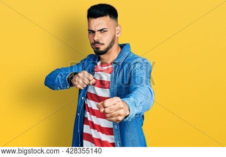 Young hispanic man with beard wearing casual denim jacket punching fist to fight, aggressive and angry attack, threat and violence