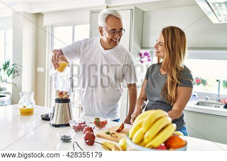 Middle age hispanic couple pouring juice on mixer machine cooking smoothie at the kitchen.