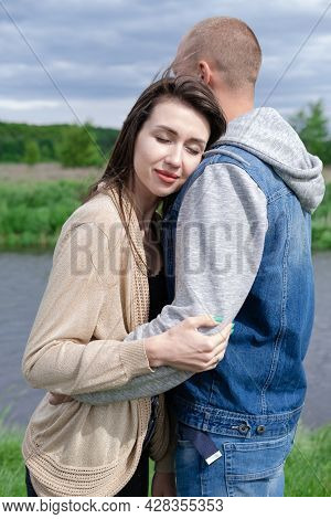 Happy Young Couple Outdoors Near Lake And Green Grass. Bald Man And Brunette Woman. Husband And Wife