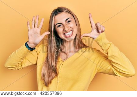 Beautiful hispanic woman wearing casual yellow sweater showing and pointing up with fingers number seven while smiling confident and happy.
