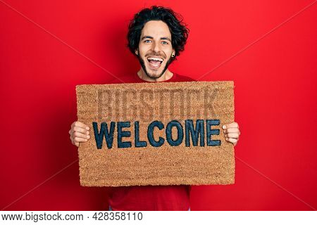 Handsome hispanic man holding welcome doormat celebrating crazy and amazed for success with open eyes screaming excited.