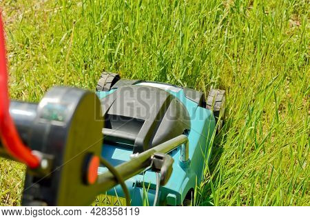 Electric Lawn Mower While Mowing A Grass And Lawn. Garden Lawn Mowing, Professional Care Service And