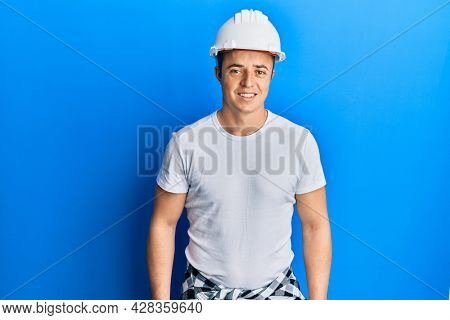 Handsome young man wearing builder uniform and hardhat with a happy and cool smile on face. lucky person.