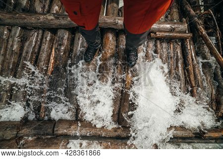 Legs Of Tourist In Red Trousers And Trekking Boots In Water Waves On Log Bridge Across Powerful Moun