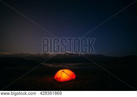 Atmospheric Mountain Landscape With Vivid Orange Tent On Hill Under Night Starry Sky. Tent Glow By O