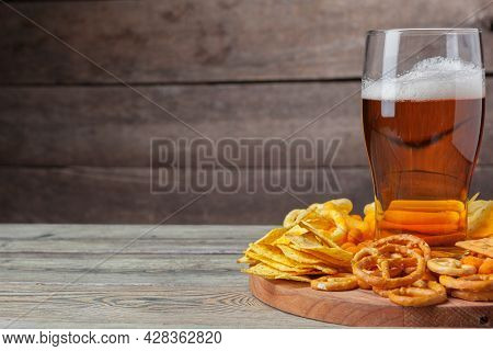 Lager Beer And Snacks On Wooden Table. Nuts, Chips, Pretzel