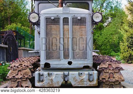 Front View Of Old Crawler Tractor. Detailed View Of Tractor. Soviet Gray Crawler. Nature Landscape B