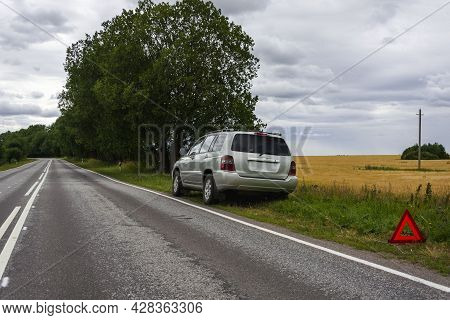 A Car Waiting For Repair After A Breakdown In A Remote Rural Area Outdoors, A Broken Car On The Side