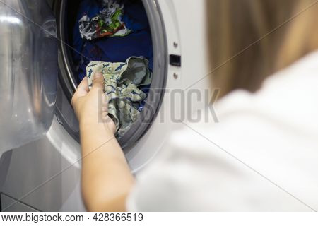 The Hand Pulls Out Of The Washing Machine The Baby's Washed Clothes. Selective Focus, Close-up