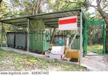 Garbage Containers In Fence Cage. Orderly Stowed Garbage Cans For Separate Garbage Collection. Envir