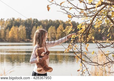 Pretty Little Girl In School Uniform With Cute Teddy Bear Holds Dry Leaf On Riverbank In Sunny Fores