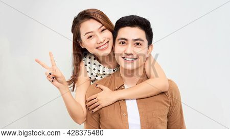 Love Forever. Young Asian Handsome Boyfriend Is Piggybacking His Cute Lover, Wearing Casual Clothes,