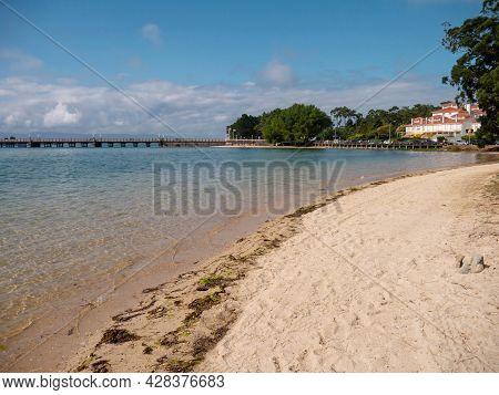 La Toja, Spain - July 24, 2021: Sandy Beach, Crystal Clear Sea And Bridge At The La Toja Island Luxu