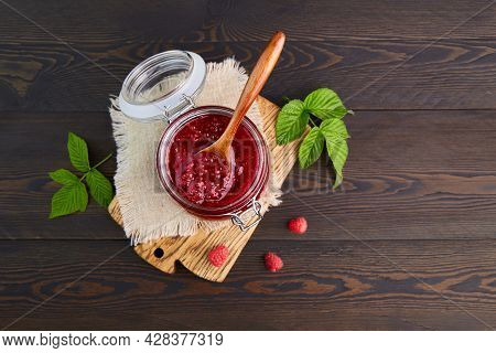 Raspberry Jam In A Glass Jar On A Dark Wooden Background. Conservation And Summer Harvesting. Top Vi