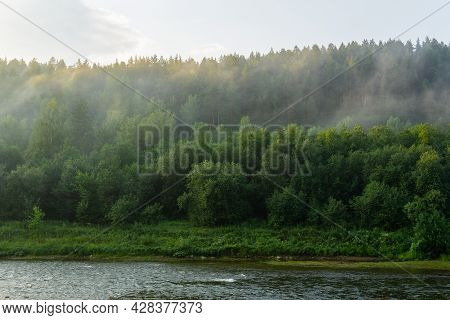 Fog In The Forest By The River. Evaporation Over The Forest In The Rays Of The Sunset. The River Ban