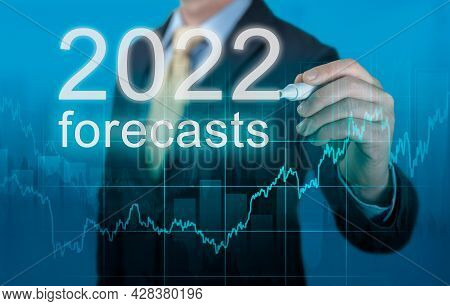 Economic Forecasts For 2022. Businessman Writes Forecasts For 2022 On A Virtual Screen. Post Covid-1