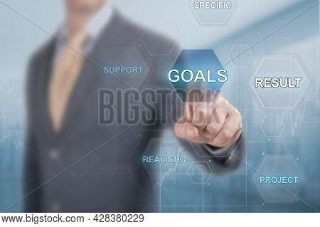 Businessman Clicks On The Goal Button On The Virtual Screen. Achieving Goals In Business Concept. Co