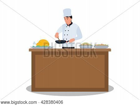The Chef Prepares The Food. Fried In A Frying Pan At The Kitchen Table, Holding A Wooden Spoon In Hi
