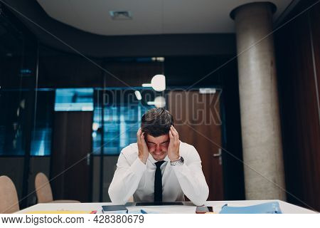 Sad Young Businessman Sit And Hold Head With His Hands At Office Table. Business People In Crisis An