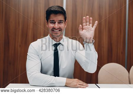 Young Businessman With Laptop At Table In Office Looking At Camera And Waving Hands. Video Conferenc