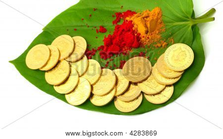 gold coins kept on betel leaf along with vermilion powder poster