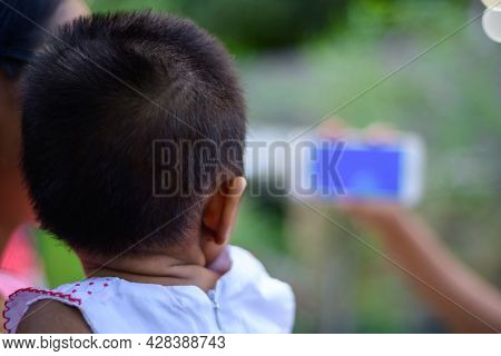 Small Baby Watching A Cartoon On A Mobile Phone, Parents Using Mobile Videos To Stop Babies Cry. The
